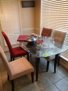 Glass Top Dining Table with Chairs and Items on top of table
